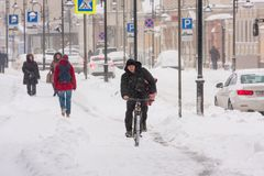 RUSSIA, MOSCOW, 4 February 2018: man riding a bycicle in heavy snowstorm in Moscow royalty free stock photos