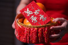 People held the Orange basket With Blessing Red Envelope for Chinese New Year Gifts. Traditional Celebration, China, Happy Chinese New Year Stock Photo