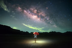People held orange umbrella under star field. Milky way, Galaxy, People held orange umbrella under star field stock photo