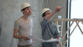 People with helmets look at the blueprints in the repair of the room. stock video