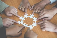 People helping in assembling puzzle, cooperation in decision making, team support in solving problems and corporate group teamwork. Concept, close up view of royalty free stock photos