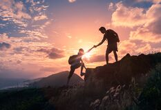 People helping each other hike up a mountain at sunrise. Giving a helping hand.