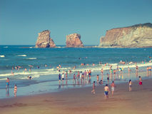 People on Hendaye beach in France, the Twins rocks Stock Photos
