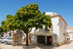 People hide in the shadow on a hot day at the street in Lagos, Portugal. Stock Image