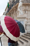 People hiding under umbrellas on a rainy day Stock Photo