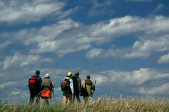 People hike in the field with blue sky and white clouds. Hikers are walking on the sky background Royalty Free Stock Photography