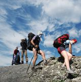 People in hiking. Four person the climb on rock royalty free stock photos