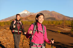 People hiking - healthy active lifestyle couple. Hikers walking in beautiful mountain nature landscape. Woman and men hikers walking during hike on volcano Stock Photos