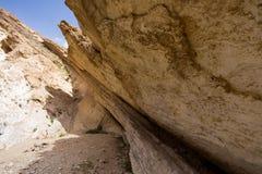 People hiking huge  desert cliff crack. Stock Photos