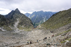 People hiking in line on the path descending from the summit of Rysy, the highest point of Poland Stock Photo