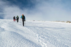 People hiking through the snowed mountains stock image