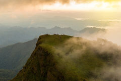 People hiking to top of mountain with flowing mist and beautiful. Sunset Royalty Free Stock Photos