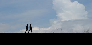 People hiking under blue sky. The silhouettes of a couple hiking under blue sky Royalty Free Stock Photos