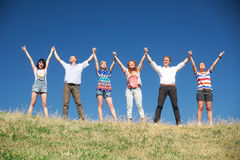 People on hill raise hands together Royalty Free Stock Images
