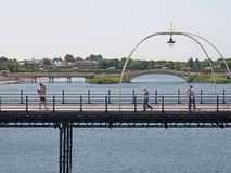 People on the historic pier in southport merseyside crossing the lake with venetian bridge and park in the background. Southport, merseyside, united kingdom - 28 stock image