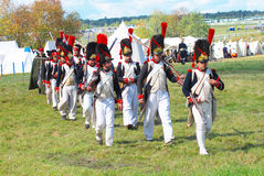 People in historical costumes march on the battle field. stock photography
