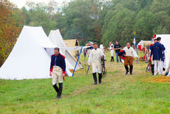People in historical costumes walks on the street. View of French camps. Stock Photo