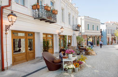 People on historical street with outdoor flower shop Stock Image