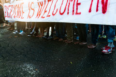People hold banner in favour of refugees during bare feet march in rome Stock Image