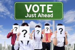 People hold question mark near the voting board. Image of unknown people covering face with question mark near the board with vote text Royalty Free Stock Image