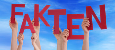 People Hold Red German Fakten Means Fact Blue Sky. Many Caucasian People And Hands Holding Red Letters Or Characters Building The German Word Fakten Which Means Royalty Free Stock Photo