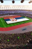 People hold Serbia flag in stadium arena. field 3d photorealistic render stock photography