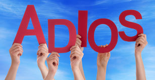 People Hold Spanish Adios Means Goodbye Blue Sky. Many Caucasian People And Hands Holding Red Letters Or Characters Building The Spanish Word Adios Which Means Royalty Free Stock Photo