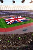 People hold United Kingdom flag in stadium arena. field 3d photorealistic render stock photo