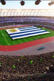 People hold Uruguay flag in stadium arena. field 3d photorealistic render stock photo