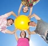 People hold yellow ball across sky Stock Images