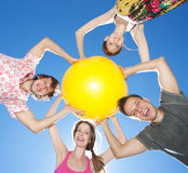 People hold yellow ball across sky Royalty Free Stock Photos