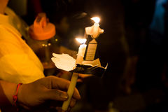 People holding candle vigil in darkness seeking hope, worship, p Royalty Free Stock Images