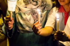 People holding candle vigil in darkness seeking hope, worship, p Stock Image