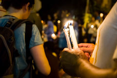 People holding candle vigil in darkness seeking hope, worship, p Royalty Free Stock Photography