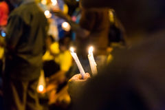 People holding candle vigil in darkness seeking hope, worship, p Royalty Free Stock Image