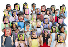 People Holding Devices with their face on it Stock Photo