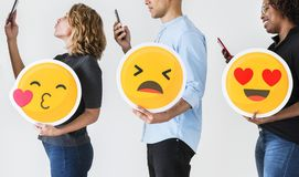 People holding emoticons and mobile devices royalty free stock photo