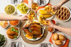 People holding glasses of wine over table with festive dinner and roasted turkey. Top view royalty free stock images