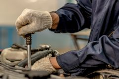 People holding hand are repairing. Image is Close up,People are repairing a car Use a wrench and a screwdriver to work Stock Images