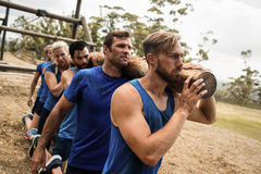 People holding a heavy wooden log during boot camp. Fit people holding a heavy wooden log during boot camp training Stock Photos