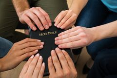 People holding holy bible Stock Image