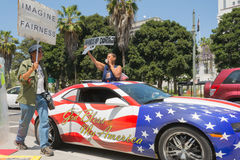 People holding sign next to a car painted in american flag color Stock Image