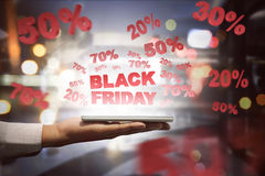 People holding tablet and showing special sale on Black Friday. Over black background Royalty Free Stock Photos