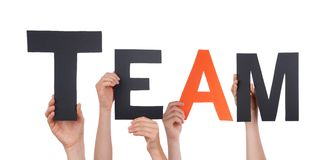 People Holding Team. People Holding a Black Team with one Orange Letter, Isolated Stock Photography