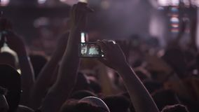 People holding their smart phones shooting video or photo stock footage