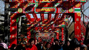 People holding toys walk under the decorated archway at temple fair in Longtanhu Park during Chinese Spring Festival in Beijing. China