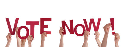 People Holding Vote Now. Many People Holding the Red Words Vote Now, Isolated Royalty Free Stock Photo