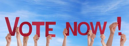 People Holding Vote Now in the Sky. Many People Holding the Red Words Vote Now in the Sky Stock Photo
