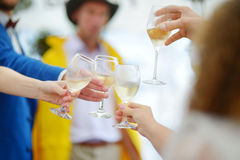 People holding wine glasses at festive event Stock Images