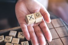 People holding wooden Tic Tac Toe game or OX game. Closeup image of people holding wooden Tic Tac Toe game or OX game Royalty Free Stock Images
